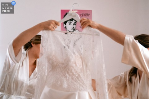 Flanders home wedding photography of getting ready:	The bride and her bridesmaid prepare the dress while Audrey Hepburn approves