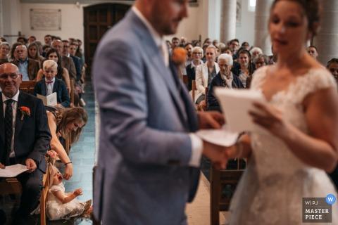 Fotógrafo de casamento em Antwerpen na igreja: Os noivos trocam votos enquanto a filha faz uma cena no corredor.