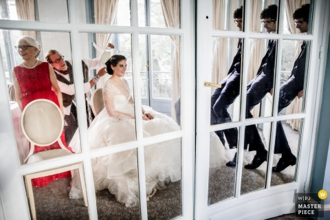 Fotografia de local de recepção de casamento - França | Noiva no espelho se preparando com seu cabelo e vestido