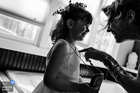 Polônia, Maine Fotógrafo de casamento: Um convidado cutuca a menina de flor de brincadeira em um casamento no Maine.