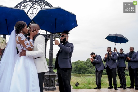 Bavaria Downs in Minnesota wedding photo: First kiss with Grooms men celebrating