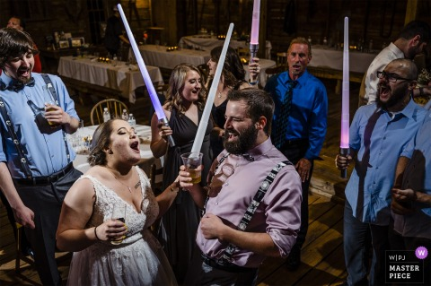 "Circle M City venue event photography | The bride and groom dance with light sabers during their wedding reception on ""Star Wars Day"""