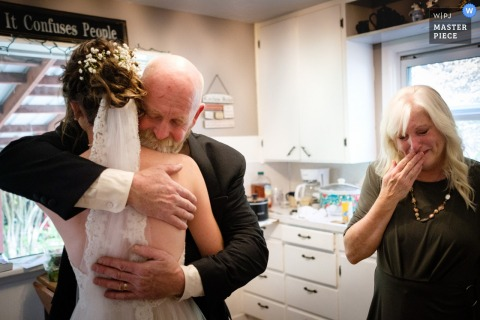 Brides family farm wedding ceremony and reception site near Kalispell Montana: A bride shares an emotional moment with her parents in the kitchen of the house where they all live before her wedding.