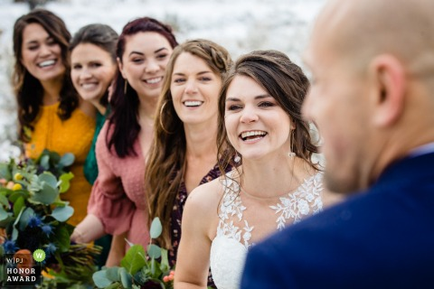 Victor, Idaho outdoor wedding ceremony photo: The bride and bridesmaids react to groom's vows