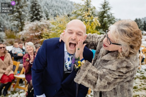 Wedding photography in the snow at Victor, Idaho   The mother of groom wipes lipstick off him after kissing at front of aisle