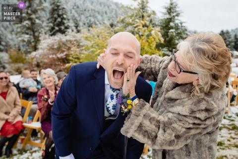 Photographie de mariage dans la neige à Victor, Idaho | La mère du marié essuie le rouge à lèvres après s'être embrassé devant l'allée