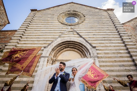 Confetti time with the beautiful church of Lucignano and tipical flags of the medieval town - Photo from Duomo di Lucignano d'Arezzo, Tuscany - Private Villa Trasimeno Lake