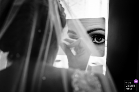 NJ photo de mariage de l'hôtel pendant la préparation | La mariée fait des ajustements de dernière minute à son maquillage dans un miroir grossissant
