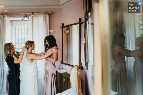 Voewood, Norfolk, Royaume-Uni reportage de mariage | La mariée et la demoiselle d'honneur partagent un moment pendant la touche finale à la préparation de la mariée