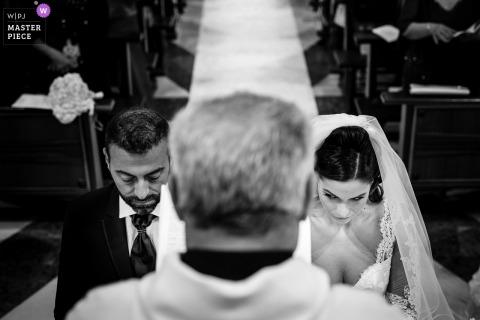 Image de la cérémonie de mariage en Calabre de la mariée regardant le marié pendant que le prêtre les bénit