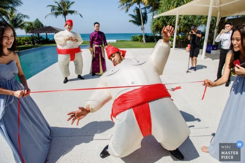 Phuket, Thailand wedding photo: Play the game of limbo in inflatable sumo wrestler suit