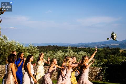 Zdjęcie przedstawiające panie na przyjęciu weselnym w Villa la Palagina podczas ceremonii wręczenia bukietu dziewczyny rzucają sobie wyzwanie
