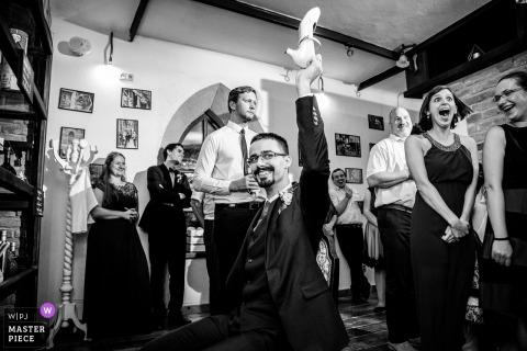 Barrio Gotico Cafe-Hochzeitsbild des Bräutigams, der einen Schuh spielt ein Aufnahmespiel hält