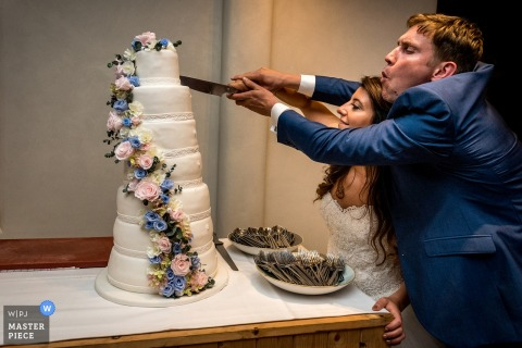 """Photographe de mariage des Flandres: """"J'aime vraiment l'atmosphère de cette photo parce que les mariés attaquent vraiment leur gâteau de mariage. J'aime leur émotion."""""""