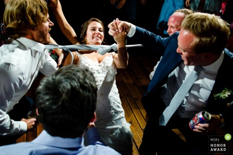 Piney River Ranch, Vail, CO wedding venue photo: The bride getting a hand from her husband while doing the limbo.