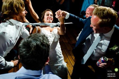 Miejsce ślubu Piney River, Vail, Kolorado Zdjęcie: Panna młoda dostaje rękę od męża podczas robienia otchłani.