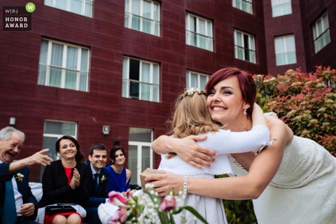 Albacete Outdoor Wedding Ceremony Photo | The bride hugs a young girl at the venue