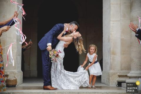 Image de la cérémonie de mariage à Paris de la mariée et du marié s'embrassant devant l'église après la cérémonie, alors qu'une jeune fille se tient fermement à la robe de la mariée, prête à descendre les escaliers.