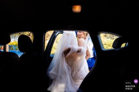 Zakynthos, photographe de mariage en Grèce: avant la cérémonie avec la mariée entrant dans la voiture avec sa grande robe