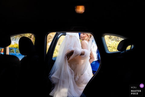 Zakynthos, Greece wedding photographer: Before the ceremony with the bride entering the car with her big dress