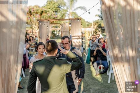 Lieu de la cérémonie de mariage en plein air: Cerimonial Sítio Santa Clara - Aracruz, Espírito Santo, Brésil - Photo du père de la mariée (officier supérieur de la police des brevets) saluant le marié (officier de l'armée brésilienne)