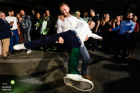 Beekhoeve Haacht wedding photojournalism   Brothers being Brothers while dancing and swinging at the reception party.