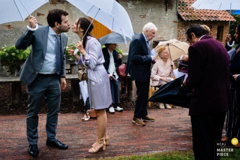 L'image de mariage de Flandre Kasteel van Brasschaat contient: Un baiser rapide par des invités sous des parapluies sous la pluie.