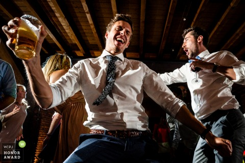 Flanders wedding photographer taking pictures on the reception dance floor of - Men being men