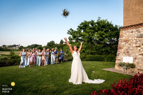 Flanders Wedding reception image contains: The bride was throwing away her wedding flowers and I love the power she's throwing the flowers away to her best girlfriends.