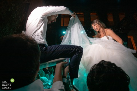 Istanbul reception venue wedding photojournalism. The groom checking under bride's skirt while up in the air