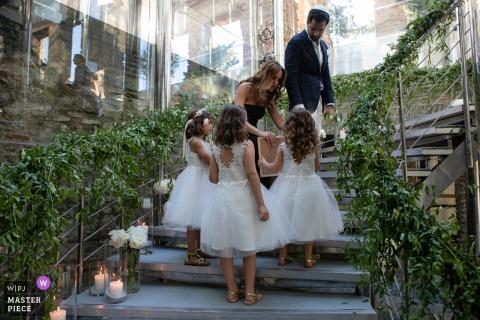 L'image de la cérémonie de mariage en Turquie contient: Une femme aide les filles à fleurir dans les escaliers menant à la cérémonie
