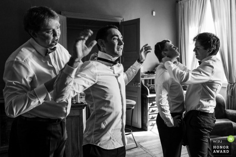 Planchevienne Castle wedding photojournalism - Groomsmen do their thing. Getting ready with their ties on.