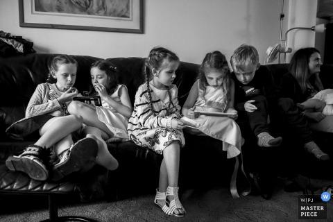 Hitchin, Hertfordshire Fotograaf: Kinderen spelen op een computer tijdens de huwelijksvieringen