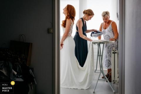 L'image de mariage à Groningen, Pays-Bas contient: La mère et la sœur de la mariée se débarrassent rigoureusement de quelques rides de la robe.