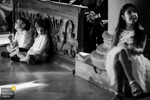 Ceremony photo in the church - Apulia - Italy - The looks and gestures between bored children during the ceremony