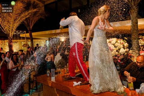 Lima Peru Wedding Reception Party Photo: The bride and groom dance on the bar table bathed in champagne