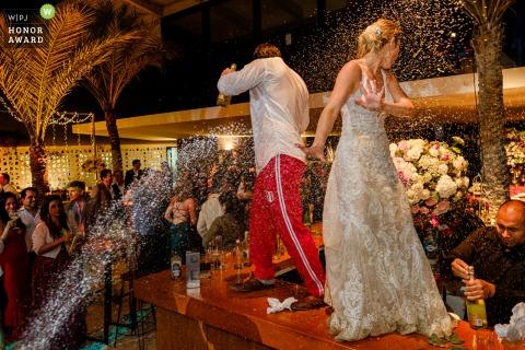 Foto de la fiesta de recepción de la boda de Lima, Perú: los novios bailan en la mesa del bar bañados en champán