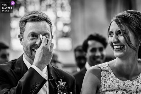 Trouwfotografie uit St Audries Park, Somerset, UK | Bruidegom die de tranen wegveegt tijdens de huwelijksceremonie, terwijl de bruid hem uitlacht