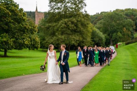 St Audries Park, Somerset, VK trouwfoto bevat: bruid en bruidegom lopen van hun kerk, op de achtergrond, naar hun locatie, met al hun gasten volgen