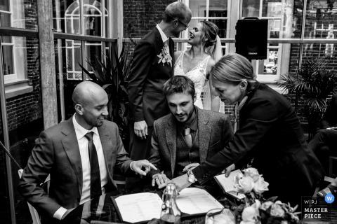 Amsterdam, Pays-Bas image de mariage: Alors que les meilleurs hommes signent le contrat de mariage, les mariés n'ont qu'un œil pour l'autre