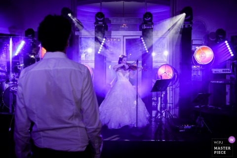 Photo de lieu de réception de mariage à Paris - France | La surprise de la mariée alors qu'elle joue d'un instrument pour le marié
