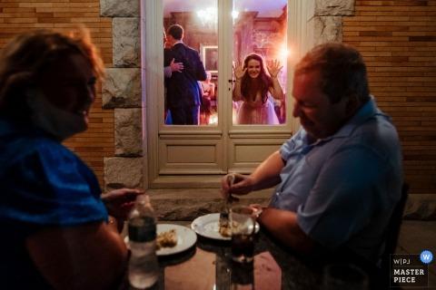 Cairnwood Estate, Huntington Valley PA - Tijdens de receptie liep ik naar buiten naar de patio om een ander perspectief te krijgen. Ik zag twee gasten genieten van de woestijn en keken naar het dansen door het raam. Net toen ik de foto moest nemen, liep de bruid naar boven