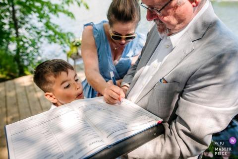 Photographie de la cérémonie en Ontario dans un chalet extérieur - Le garçon regarde des témoins signer les papiers