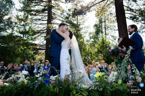 West Shore Cafe, Lake Tahoe CA Huwelijksfotograaf: kus van bruid en bruidegom aan het einde van de buitenceremonie onder de bomen.