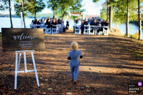 Calabogie Peaks Resort, Hochzeitsfotos von Calabogie Ontario: Ring Bearer macht den Solo-Spaziergang zur Outdoor-Zeremonie unter den Bäumen am See.