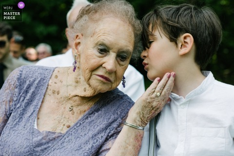 L'image de Glen Falls House, Round Top, NY contient: Une arrière-grand-mère écoute doucement son arrière-petit-fils alors qu'il lui murmure à l'oreille lors d'une cérémonie de mariage.