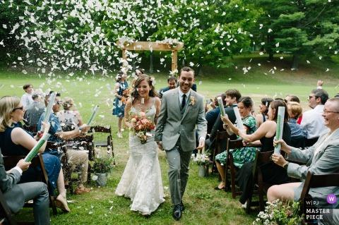 Glen Falls House, Round Top, NY photo de mariage: Une mariée et le marié se retirent joyeusement de l'allée à la fin de leur cérémonie de mariage pendant que les invités tirent sur eux des canons à confettis.