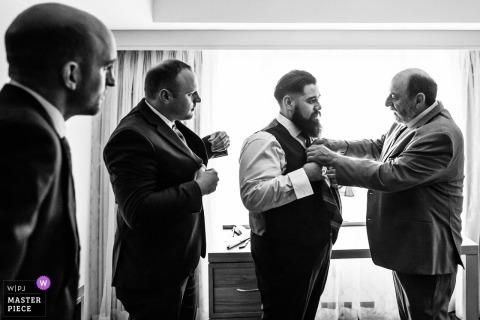 Trouwfoto: vader en groomsmen helpen bruidegom met stropdas bij bruiloft The Manor, West Orange, New Jersey
