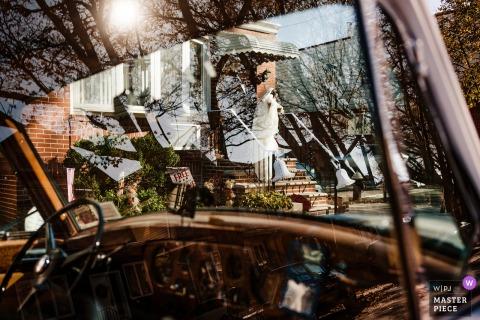 Photographie de mariage à New York: la mariée quitte la maison, comme on le voit à travers le pare-brise avant de cette voiture de transport de mariage vintage.