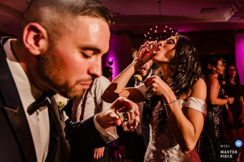 Venue: Royalton on the Greens | Bride and groom take shots in this wedding picture